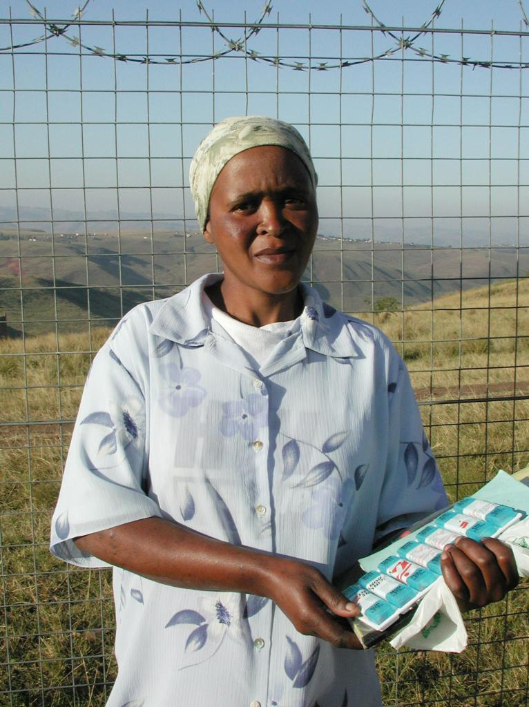 Nozuko Mavuka, an HIV-positive mother in the Lusikisiki district of South Africa's Eastern Cape, clutches the pillbox that restored her failing health. Mavuka is one of several hundred villagers receiving antiretroviral treatment through a community-based program launched by Doctors Without Borders/Médecins Sans Frontières and the Treatment Action Campaign. © 2005 Geoffrey Cowley, Courtesy of Photoshare