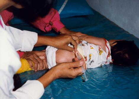 An infant in Indonesia receives an immunization. © 1999 Anne Palmer, Courtesy of Photoshare