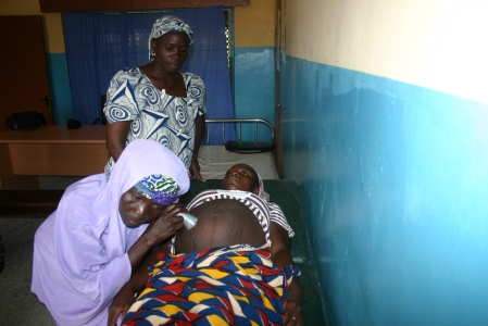 TBA Hauwa Saliu listens to fetal heart sounds under the supervision of Faustina Ajayi, a nurse-midwife